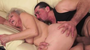 A corpulent granny is receiving a young cock in her hairy old cunt